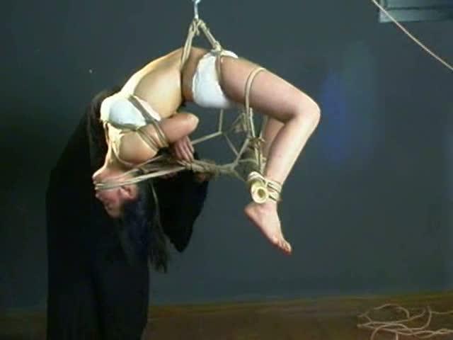 緊縛師の手によって淡々と縛り上げられるM女。猿轡を付けられエビ反りや逆さで吊り上げられ汗だくで顔を赤くし悶える。